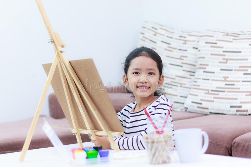 Little girl smiling and drawing a picture of a dreaming at home. A little girl smiling and drawing a picture of a dreaming at home royalty free stock photo