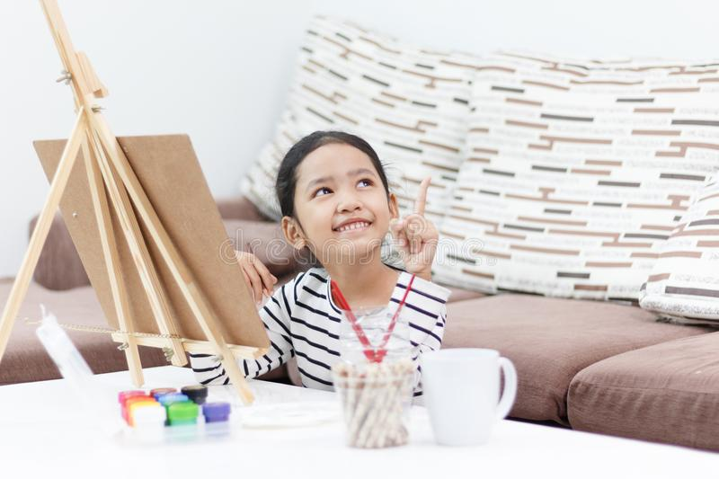 Little girl smiling and drawing a picture of a dreaming at home. A little girl smiling and drawing a picture of a dreaming at home and get idea royalty free stock image