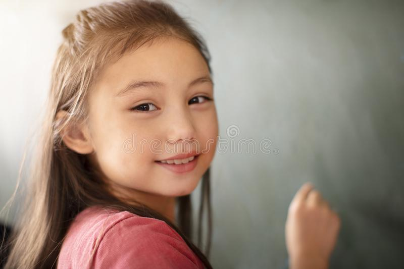 girl smiling in front of chalkboard royalty free stock image