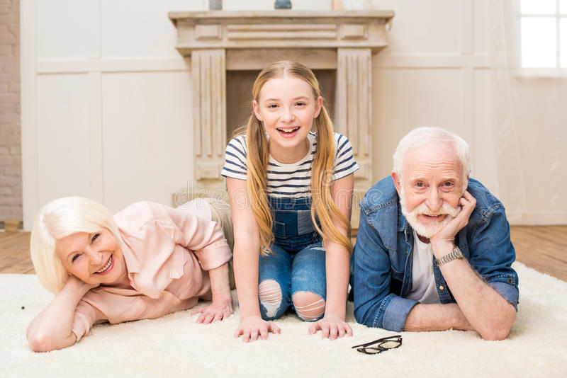 Little girl with smiling grandpa and grandma resting together at home royalty free stock photos