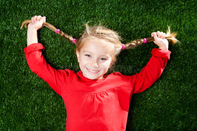 Little girl smiling on grass. Little girl smiling on a green lawn royalty free stock photography