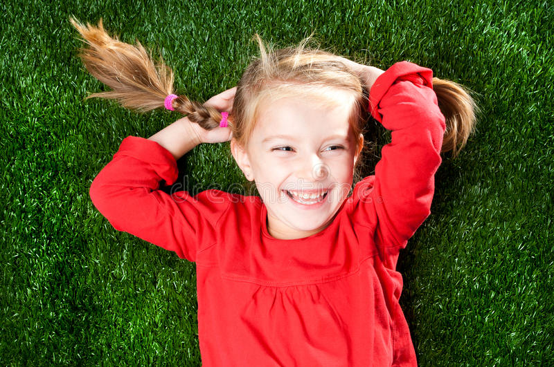 Little girl smiling on grass. Little girl smiling on a green lawn royalty free stock photo