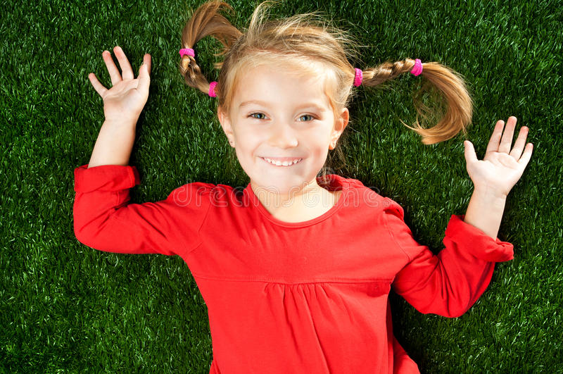 Little girl smiling on grass. Little girl smiling on a green lawn stock photography