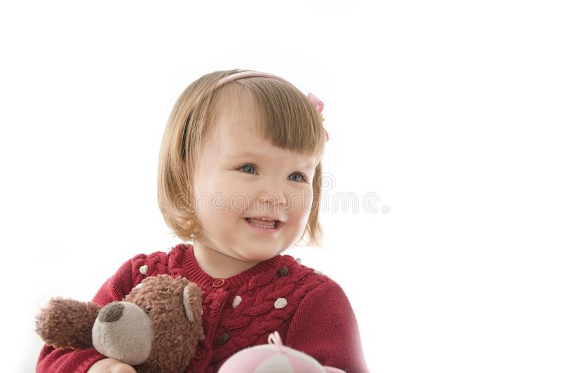 Little girl smiling happy. cute caucasian baby with bear and doll  on white background royalty free stock photos
