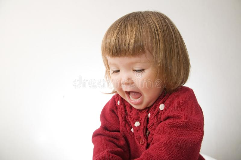 Happy funny little girl emotional playing. cute caucasian blond baby girl with bear and doll stock photos