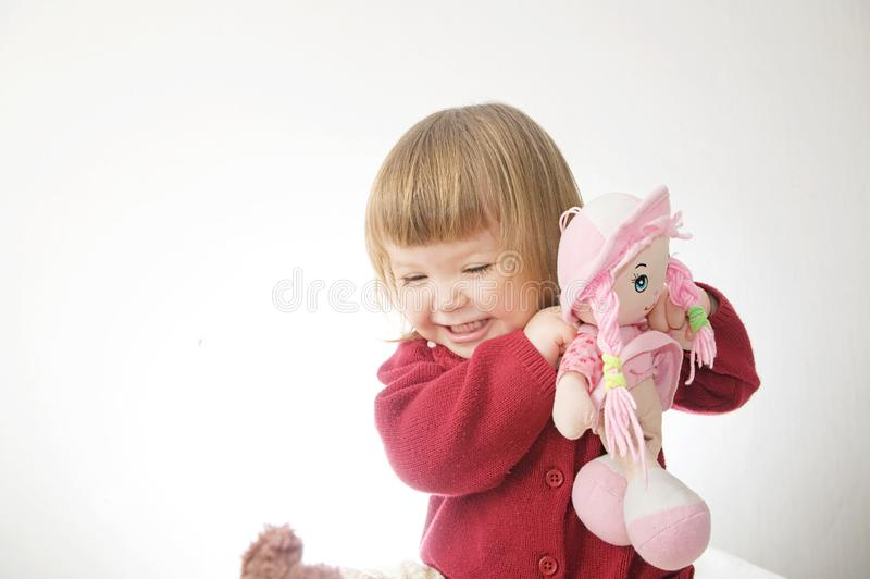 Little girl smiling happy. cute caucasian baby with bear and doll isolated on white background stock photos