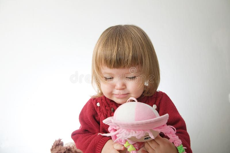 Little girl smiling happy. cute caucasian baby with bear and doll isolated on white background royalty free stock image