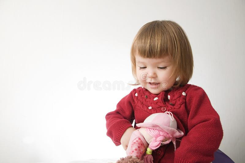 Little girl smiling happy. cute caucasian baby with bear and doll isolated on white background stock images