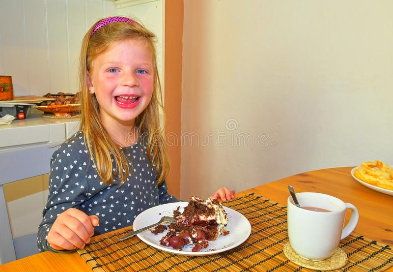 Little girl smiling on her birthday. Small girl celebrating her six birthday. Birthday cake and little girl. Girl eating birthday stock photography
