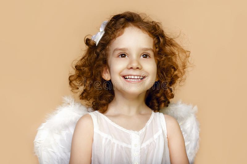 Little girl smiling, looking at a side, with wings in white dress, over beige background. Valentines day cupid. stock photography