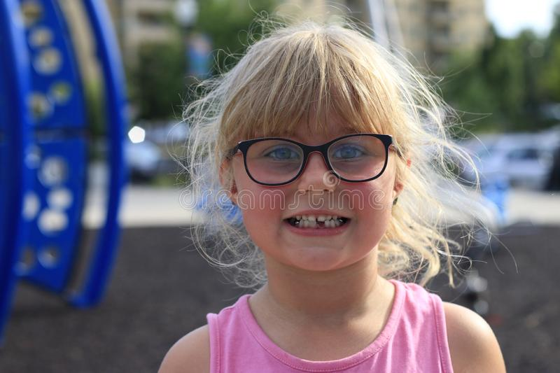 Little girl smiling outside showing her missing middle tooth. Little girl outside showing her missing middle tooth and is proud royalty free stock images