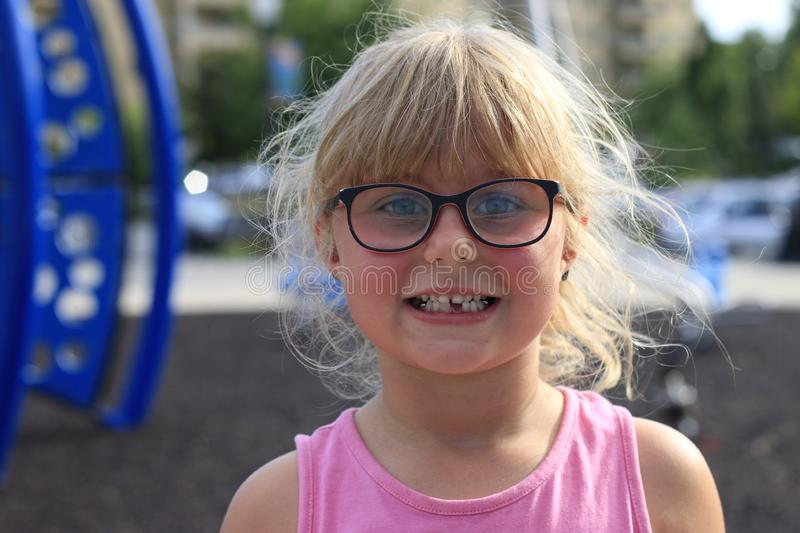 Little girl smiling outside showing her missing middle tooth. Little girl outside showing her missing middle tooth and is proud stock photos