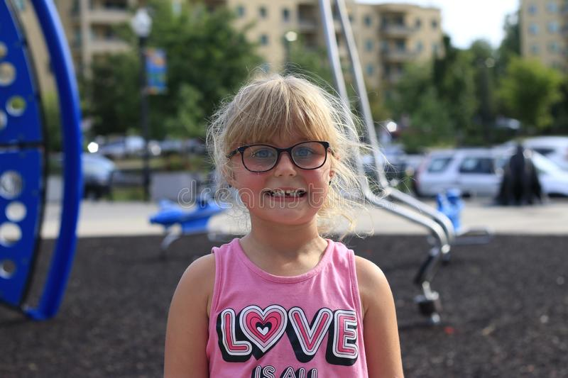 Little girl smiling outside showing her missing middle tooth. Little girl outside showing her missing middle tooth and is proud royalty free stock photography
