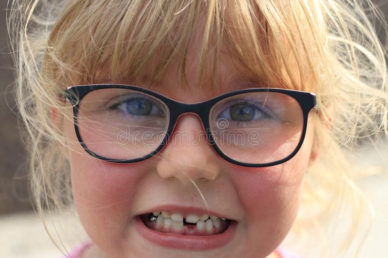 Little girl smiling outside showing her missing middle tooth. Little girl outside showing her missing middle tooth and is proud stock photography