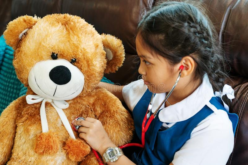 Little girl is smiling and playing doctor with brown bear and stethoscope. Kid and health care concept. stock image
