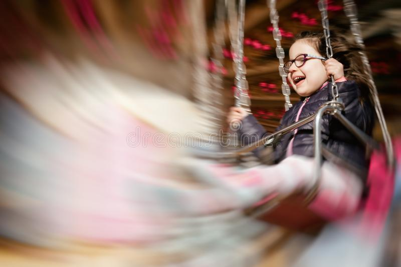 Little girl smiling while riding a carrousel; intentional motion blur effect. Panning shot of a little girl smiling while riding a carrousel; intentional motion stock photography