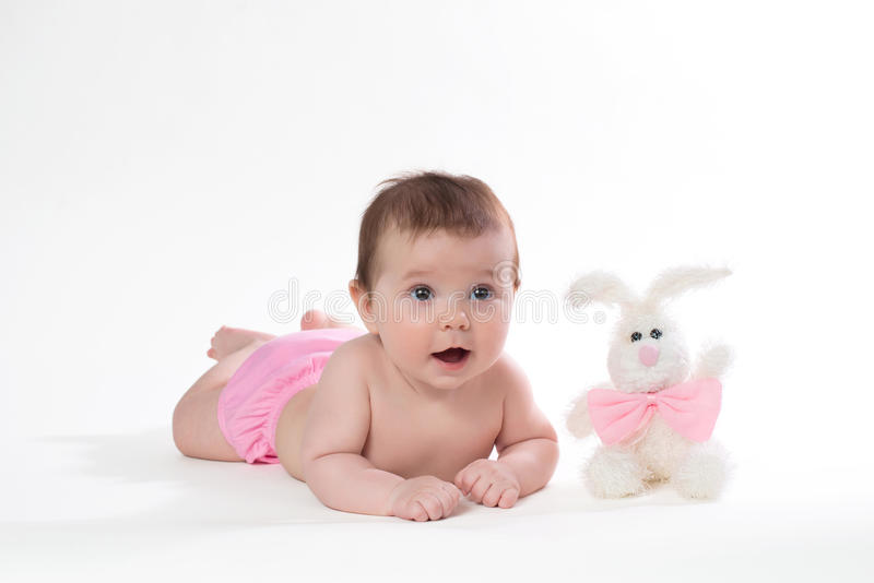 Little girl smiling with a toy rabbit lies on white background. stock image