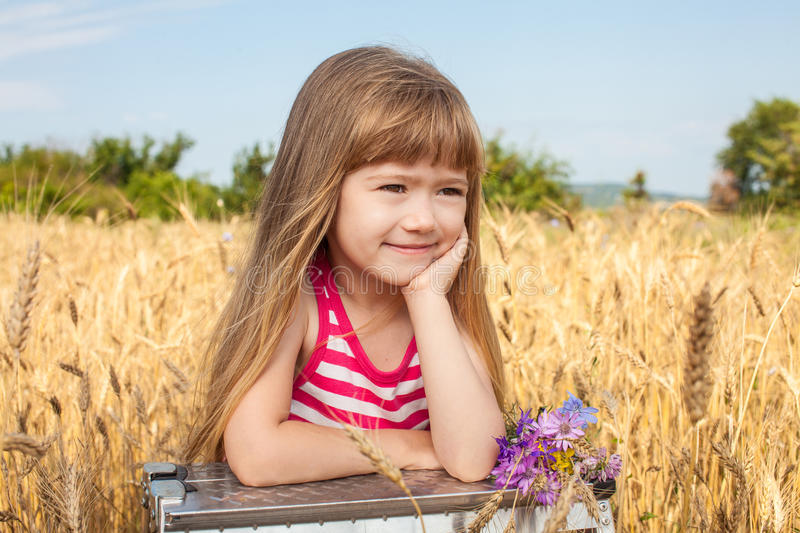 Little girl smiling in the wheat field royalty free stock image