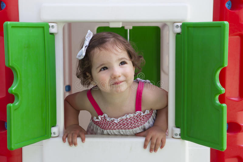 Little girl smiling through the window of kids playhouse royalty free stock photo