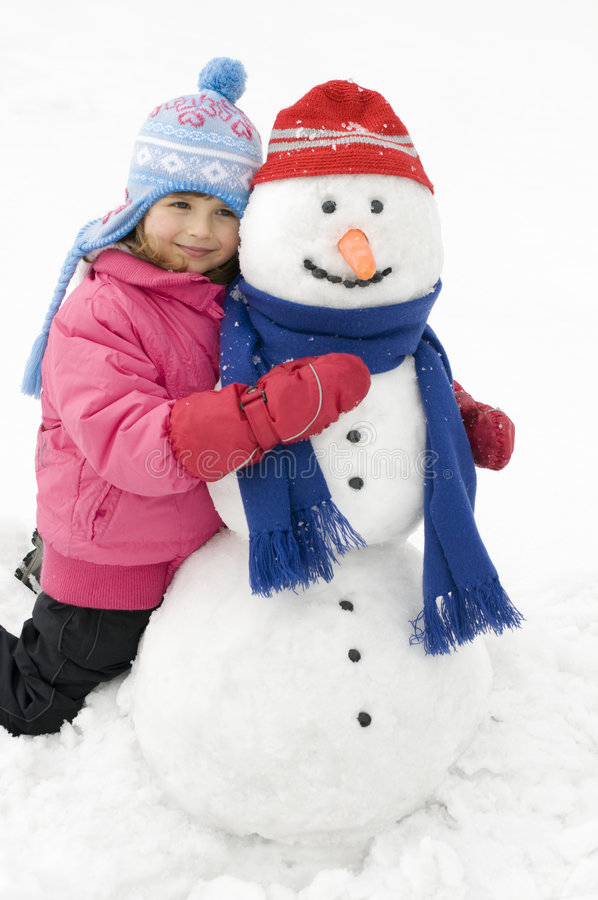 Little girl and snowman stock photos