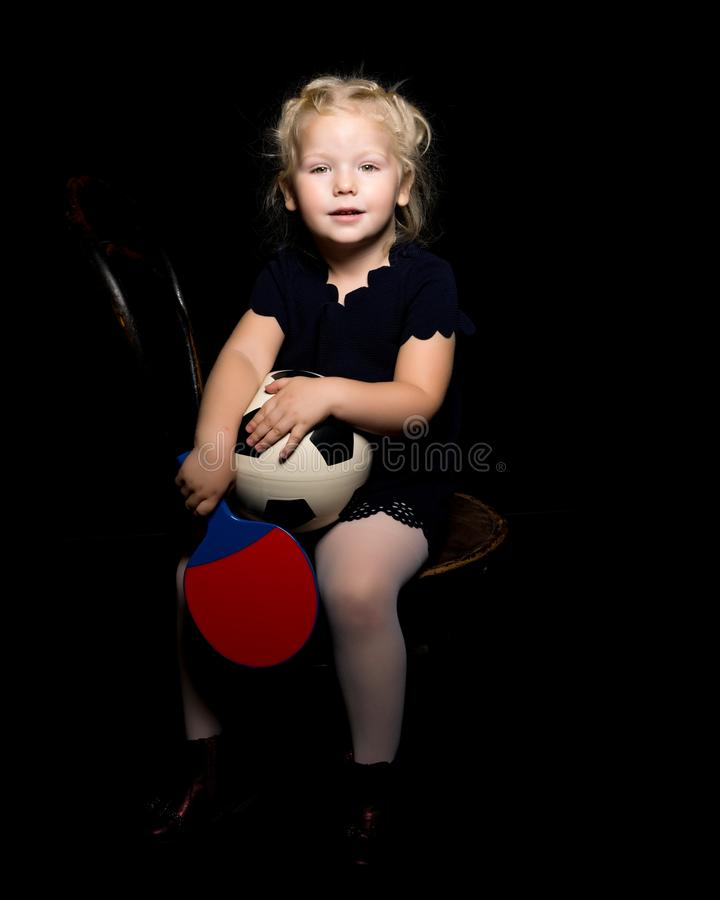 Little girl with a soccer ball on a black background. stock images
