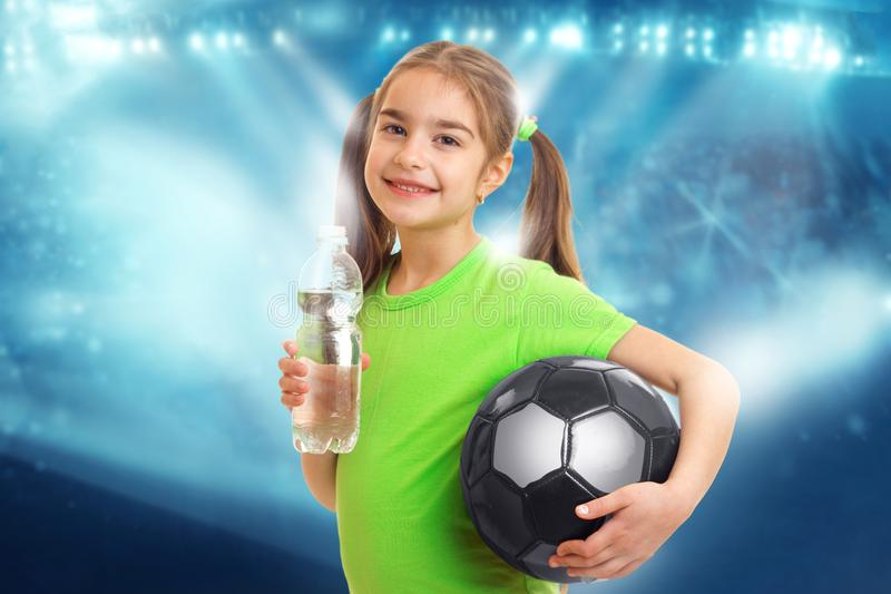 Little girl with soccer ball in hands drinks water royalty free stock images