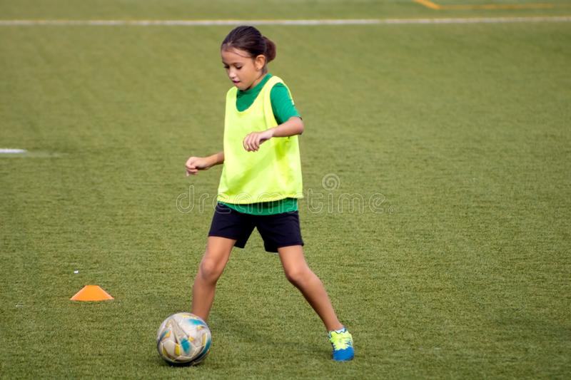 Little girl in a soccer training. In Burriana, light, beautiful, cute, game, ball, player, girls, kid, practice, tired, female, childhood, youth, exercise royalty free stock photo