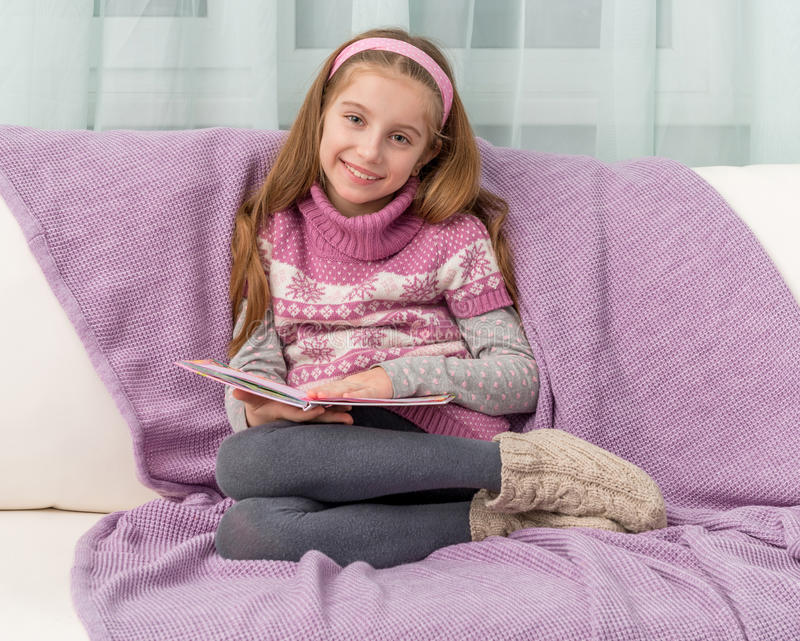 Little girl on sofa with the book royalty free stock photos