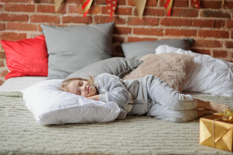 Little girl in a soft pajamas has fallen asleep. stock photography