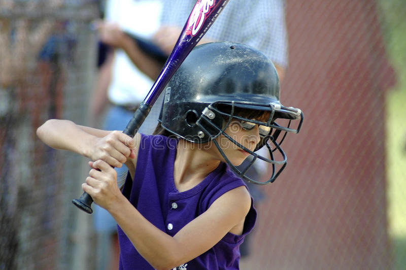 Little girl with softball helmet up to bat royalty free stock photography