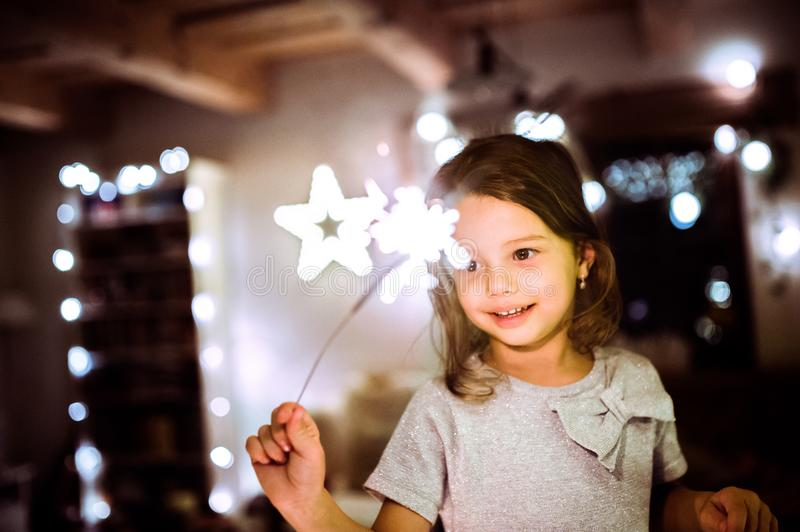 Little girl with a sparkler at Christmas time. royalty free stock photo