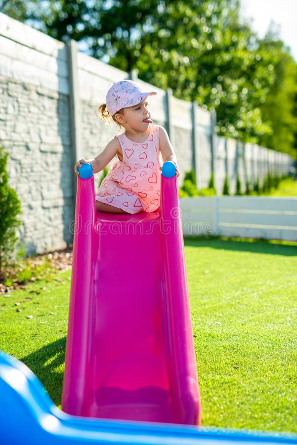 Little girl spending fantastic time on playground. Happy childhood. Authentic image. Baby, toddler, caucasian, kid, park, fun, outdoor, summer, joy, cute stock photography