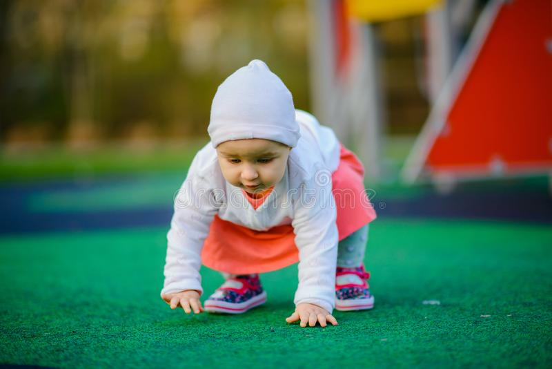 Little girl spending fantastic time on playground. Happy childhood. Authentic image. First walk, steps. Baby, toddler, caucasian, kid, park, fun, outdoor stock images
