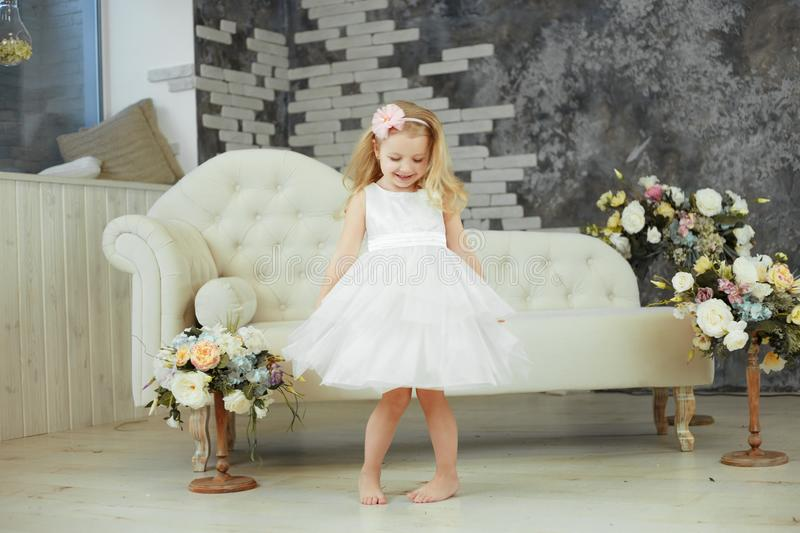 Little girl are spining in white luxury dress stock image