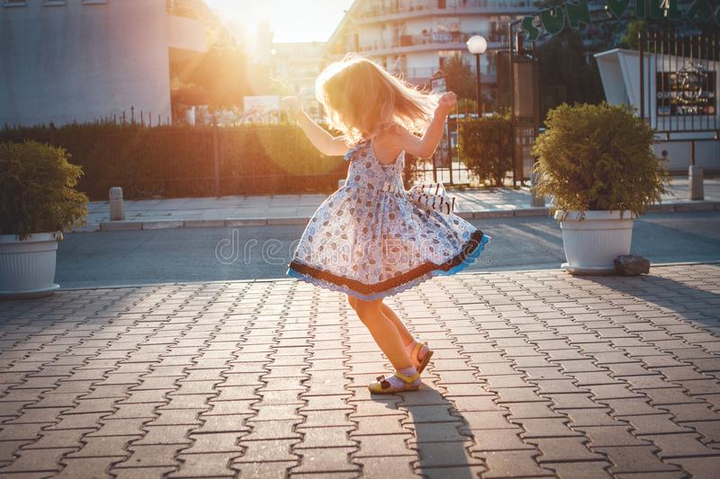 Little girl spinning around him in the street royalty free stock images