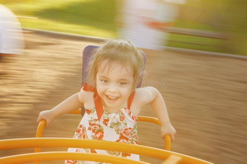 Little girl spinning on a children`s carousel among the playground. royalty free stock photo