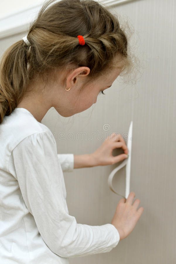 Little girl spoiled the wallpaper. stock photo