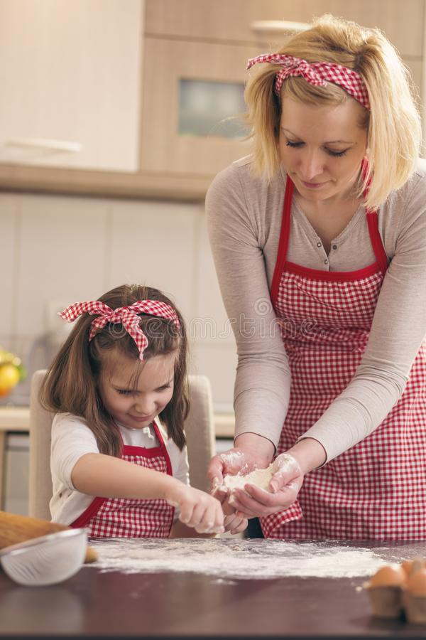 Little girl sprinkling flour on the kitchen table royalty free stock images
