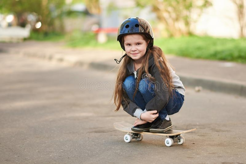 A little girl squats on a skateboard. For any purpose royalty free stock photos