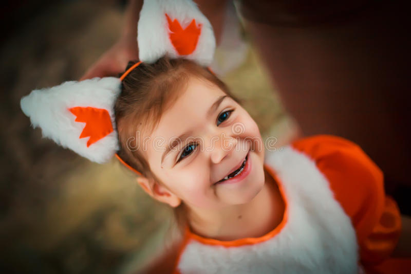 A little girl in a squirrel suit with huge white ears. Child in stock image