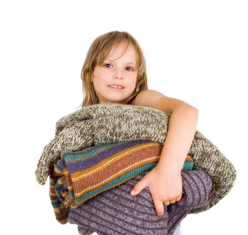 Little girl with stack of sweaters royalty free stock images