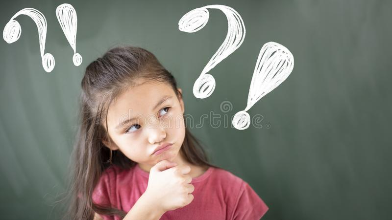 girl standing against chalkboard with question mark royalty free stock photos