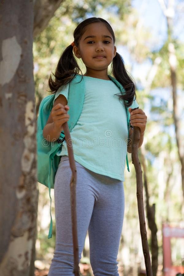 Little girl standing with backpack holding walking sticks in her hands royalty free stock image
