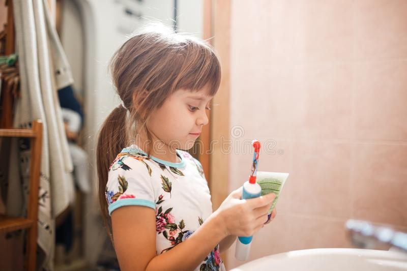 Little girl is standing in the bathroom holding a toothpaste and a toothbrush stock photos