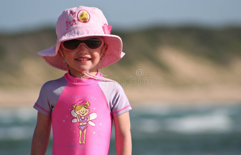 Little Girl standing on the beach stock photo