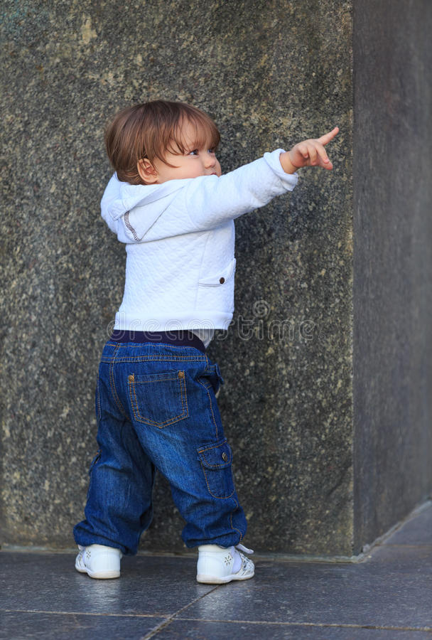 Little girl is standing being hold the marble wall and pointing to the side with her index finger stock images