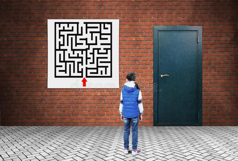 A little girl is standing in front of the labyrinth plan and a closed door. Forthcoming difficulties. A little girl is standing in front of the labyrinth plan stock photos