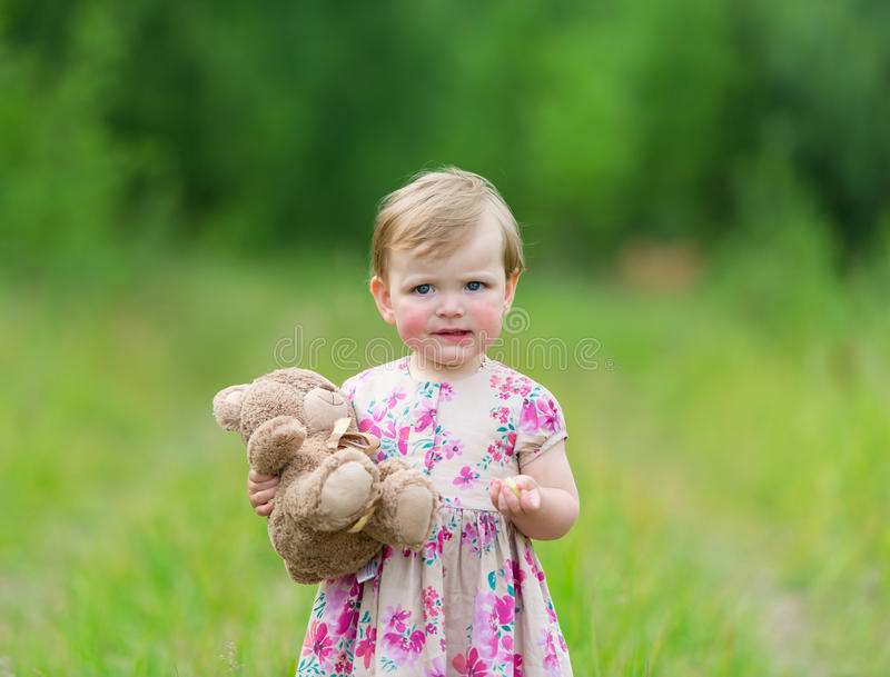 Little girl standing in grass holding large teddy bear. Little cute girl standing in the grass holding large teddy bear with sunset light. The child eats a stock photo