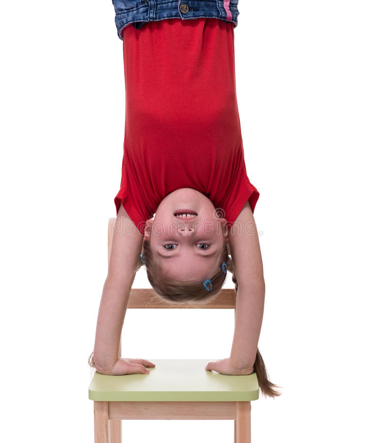 Little girl standing on her hands on chair