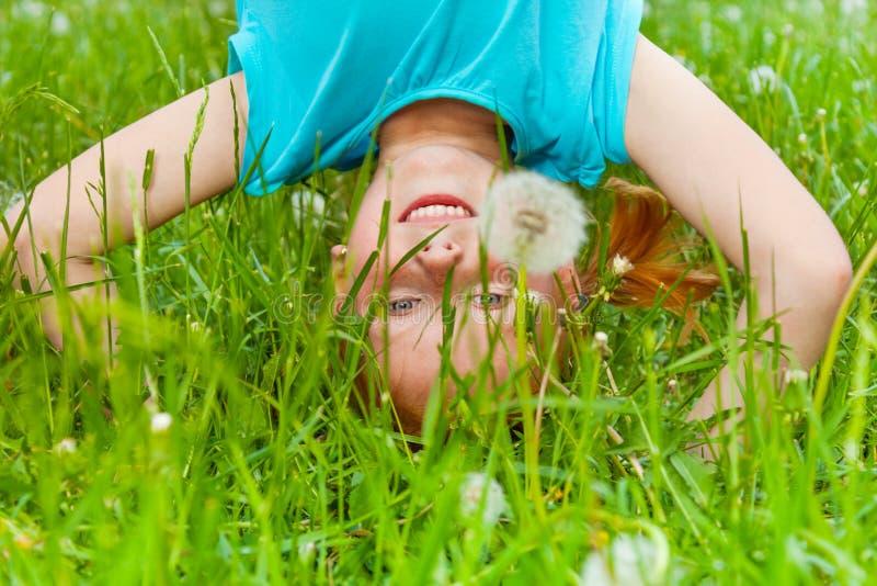 Little girl standing on her head. Little smiling girl standing on her head on the grassy meadow stock photography